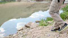 Hiker sitting down by a stream Stock Footage