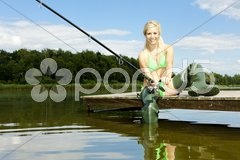 Fishing woman sitting on pier Stock Photos