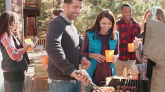 Friends stand talking at a barbecue, one tends to the grill Stock Footage