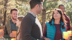 Friends stand talking at a barbecue, one grilling, close up Stock Footage