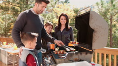 Family barbecuing on a deck in the forest Stock Footage