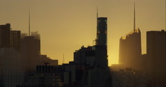 Morning sun rises behind large New York City skyscraper and construction site Stock Footage