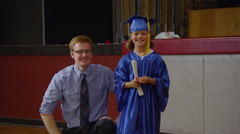Teacher with young girl graduating with diploma Stock Footage