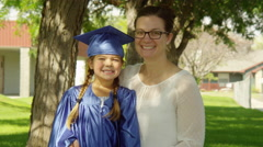 Portrait of mom and young girl in graduation with diploma Stock Footage