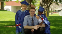 Teacher with two students during graduation with diplomas Stock Footage
