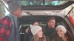 Friends talking at the open back of a car, close up Stock Footage
