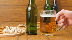 Composition of beer, crackers, pistachios, dried fish. A hand grabs a beer Stock Footage