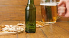 Composition of beer, crackers, pistachios, dried fish. A hand puts beer Stock Footage