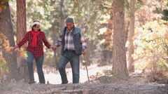 Senior couple in a forest walk to camera, on left of frame Stock Footage