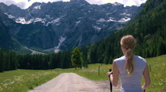 Walking behind young woman on a hike to the mountains with poles in spring Stock Footage