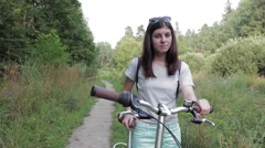 Girl With Bicycle Looking at Camera Stock Footage