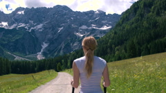 Mid shot - Walking behind young woman on a hike to the mountains with poles Stock Footage