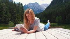 Young woman lying on pier at the lake with tablet in her hands Stock Footage