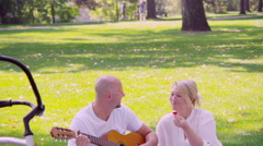 Man serenades woman with guitar in the park Stock Footage