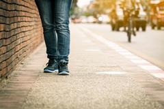 Closeup of young woman legs walk on sidewalk Stock Photos