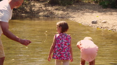 Mom and son looking at fish in the stream Stock Footage