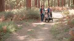 Male parents pushing stroller with two kids through a forest Stock Footage
