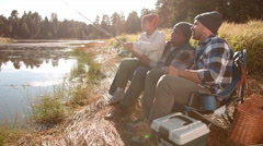 Grandfather and father sit showing boy how to fish by a lake Stock Footage