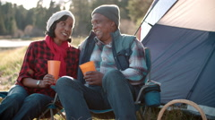 Senior black couple on camping trip outside tent, close up Stock Footage