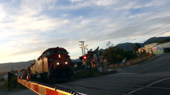 Freight train approaching crossing Stock Footage
