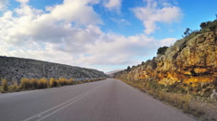 Point of view vehicle drive car countryside road rocky clouds blue sky day POV Stock Footage
