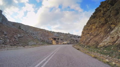 Point of view vehicle drive rocky scenery house ruins car travel road day POV Stock Footage