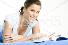 Portrait of lying down woman with a journal Stock Photos