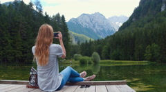 Young woman sitting on pier at the lake with a phone and taking photos Stock Footage