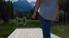 Walking behind woman arriving to the lake beneath mountains Stock Footage