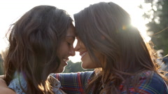 Lesbian couple embrace touching noses, eyes closed, close up Stock Footage