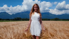 Young woman in white dress walking in yellow wheat field and looking into camera Stock Footage