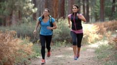 Two young women running in a forest, close up Stock Footage