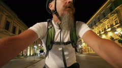Man with beard riding bicycle at night in town Stock Footage