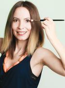 Woman applying eyeshadow with makeup brush Stock Photos