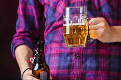 Man holds glass of beer. Stock Photos