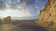 POV vehicle drive coastal winding curvy road rocky sunny sky car point of view Stock Footage