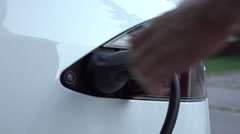 CLOSE UP: Businessman unplugging Tesla electric car from charging station Stock Footage