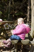 Little girl sitting on bench Stock Photos