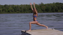 Yoga wide angle pose at end of dock Stock Footage
