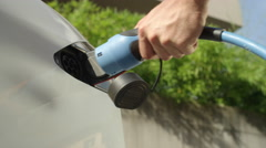 CLOSE UP: Young man unplugging Tesla car from electricity grid on sunny day Stock Footage