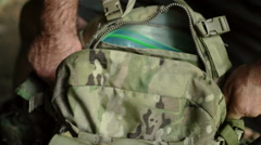 Man Zips up a Camo Backpack Stock Footage