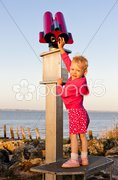 Standing little girl by telescope Stock Photos