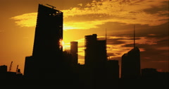 Sun rises behind silhouetted skyscrapers in bright yellow morning sky Arkistovideo