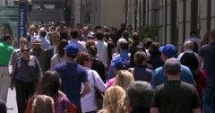 New York City pedestrians pass by one another on busy city sidewalk Stock Footage