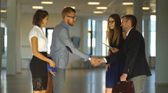 Four business people handshake in office lobby Stock Footage