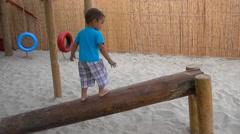 Child walks on beam learning balance Stock Footage