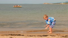 A boy playing in ocean water on beautiful beach Stock Footage