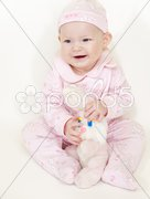 Sitting baby girl with a rabbit toy Stock Photos