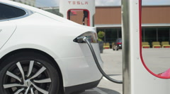 CLOSE UP: White electric car loading batteries fast at Supercharger Stock Footage