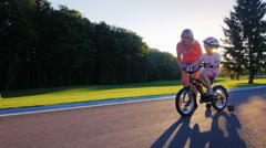 Mom plays with her daughter in the park. He teaches her to ride a bike on the Stock Footage